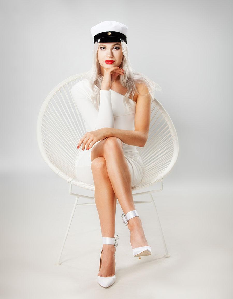 Ylioppilaskuvaus valkoisella taustalla tuolilla istuen studiolla Turussa.